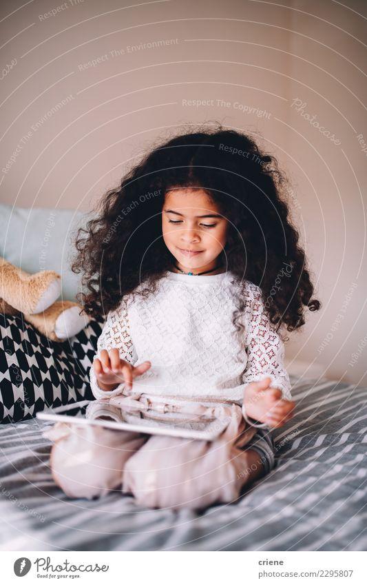 Kleines afrikanisches Mädchen, das zu Hause Spiel auf digitaler Tablette spielt Glück schön Spielen Kind Schule Computer Technik & Technologie Internet Mensch