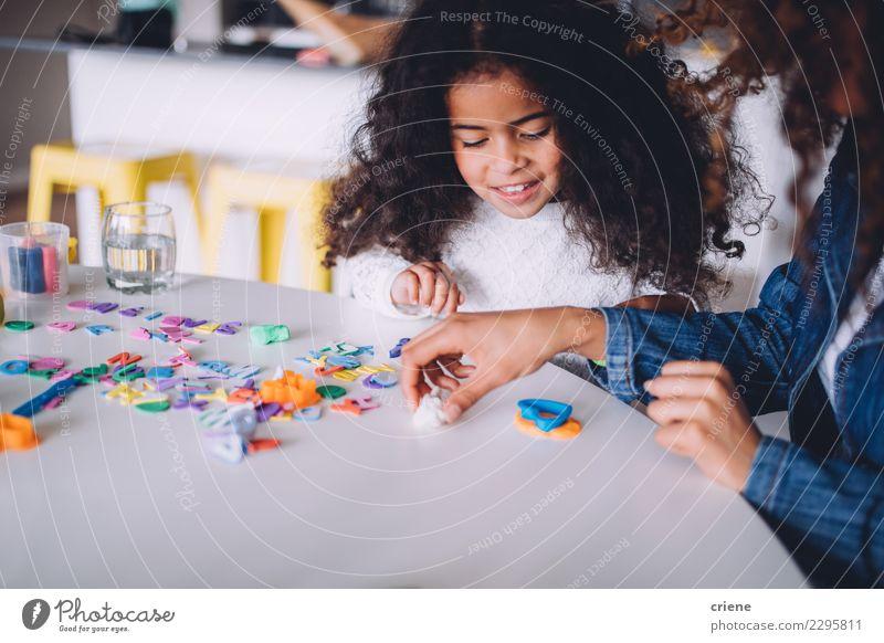 Kleines afrikanisches Mädchen, das zu Hause mit Lehm spielt Freude Glück Spielen Tisch Kindergarten Schule Frau Erwachsene Eltern Mutter