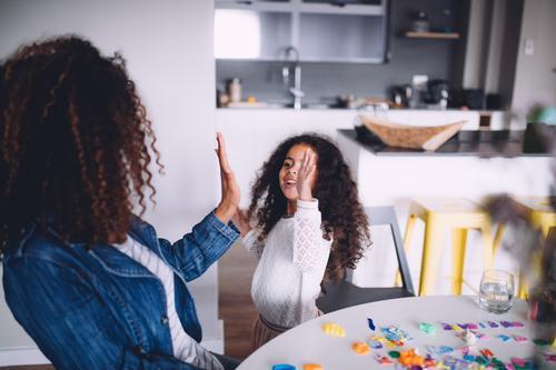 Mutter und Tochter, die Hoch fünf geben Kind Frau Freude Erwachsene Familie & Verwandtschaft Glück Spielen Schule Zusammensein Kindheit Tisch niedlich Papier