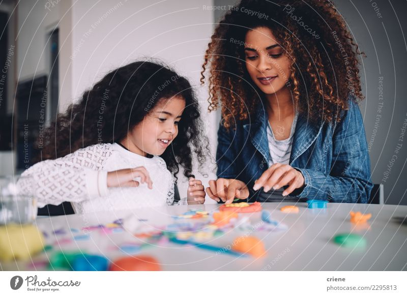 Afrikanische Mutter und Tochter, die zusammen mit Spielwaren spielen Freude Glück Spielen Tisch Kindergarten Schule Frau Erwachsene Eltern