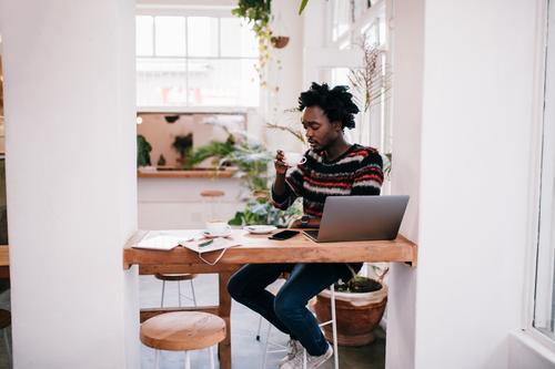 Afrikanischer junger Mann, der mit Laptop in der Kaffeestube arbeitet kaufen Glück Restaurant Arbeit & Erwerbstätigkeit Business Computer Notebook