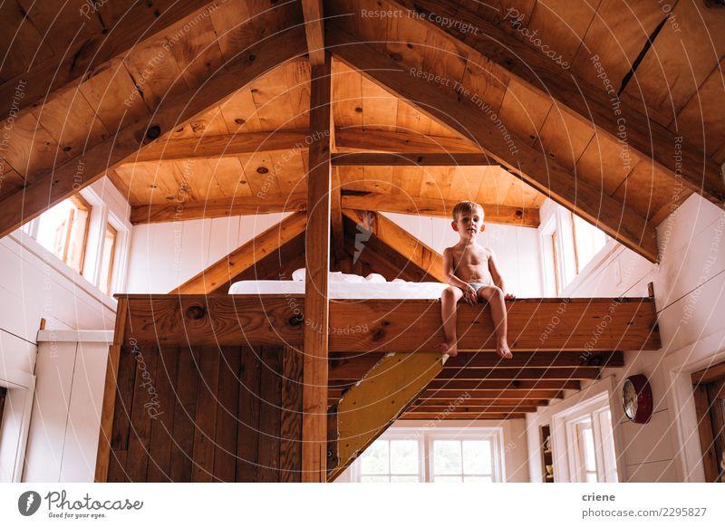 Netter kleiner kaukasischer Junge, der auf die Oberseite im hölzernen Dach sitzt Lifestyle Glück schön Haus Kind Mensch Mann Erwachsene Kindheit Hütte Holz
