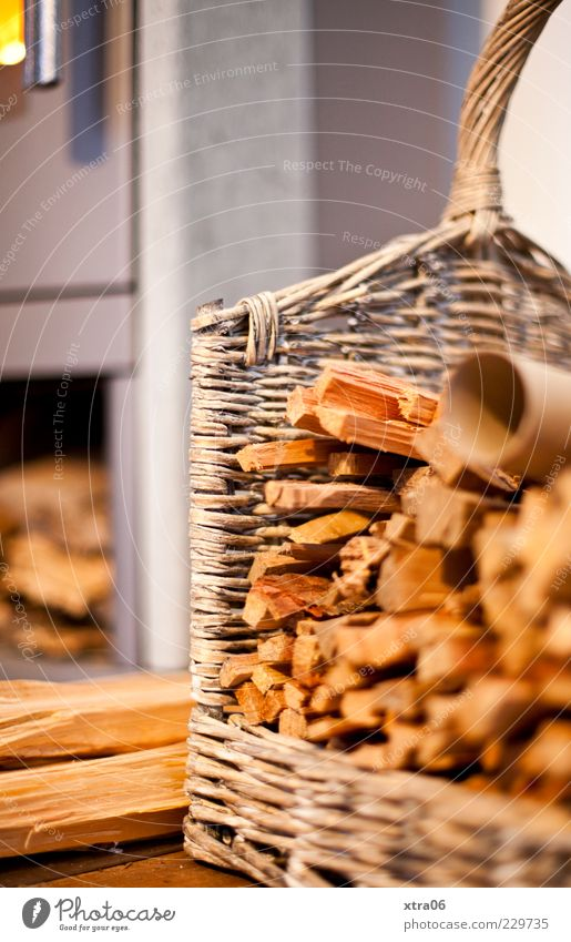 wärme Holz braun Korb Brennholz Kamin Farbfoto Innenaufnahme Menschenleer Textfreiraum links Textfreiraum oben Unschärfe Detailaufnahme Holzstapel