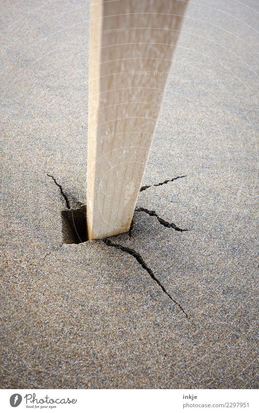 Unlackierter Pfahl steckt im nassen Sandboden mit Riß. Strand Holz kaputt Boden Riss Pfosten beweglich roh Holzpfahl Stabilität losgelöst stecken wackelig