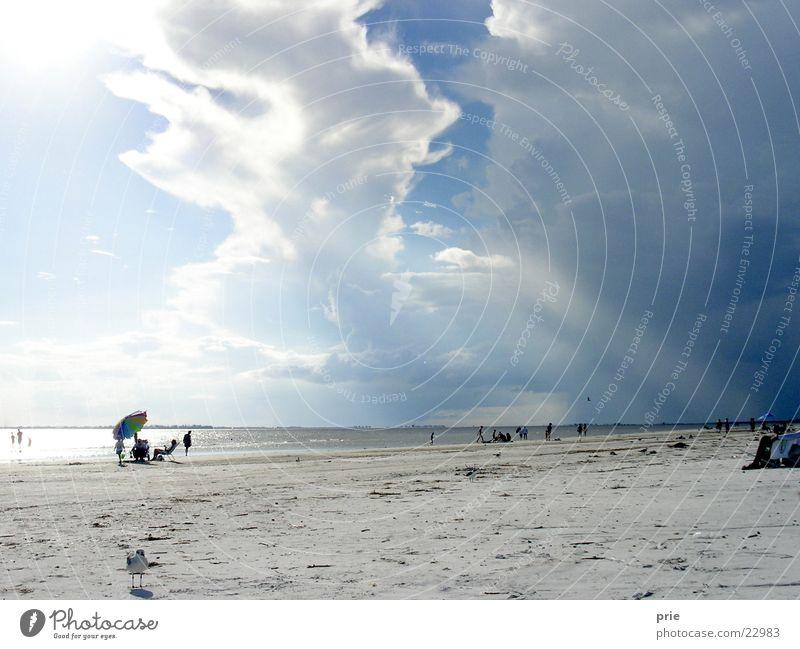 Aufbruchsstimmung Sturm Wolken Strand Meer Sand Regenschirm Sonne Gewitter