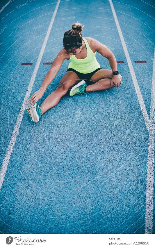 Junger weiblicher Athlet, der auf blaue Laufbahn ausdehnt Lifestyle Sport Leichtathletik Erfolg Joggen Stadion Rennbahn Mensch Frau Erwachsene Konkurrenz