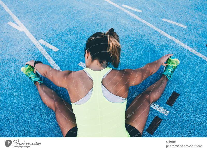 Fit Frau, die sich auf blauer Laufbahn vor dem Laufen dehnt. Lifestyle Sport Leichtathletik Erfolg Joggen Stadion Rennbahn Mensch Erwachsene Konkurrenz Beine