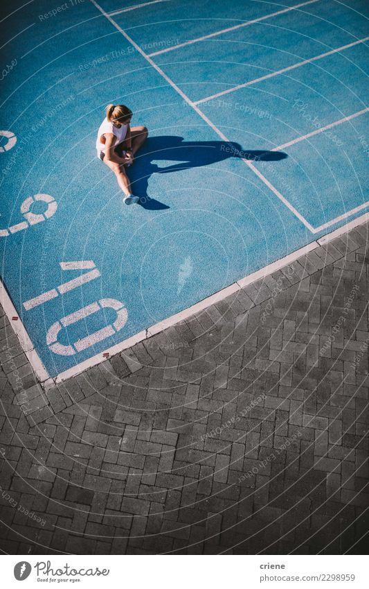 Geeignete athletische Frau, die nach hartem Training auf Laufbahn stillsteht Lifestyle Sport Leichtathletik Erfolg Stadion Mensch Erwachsene Schuhe Fitness blau