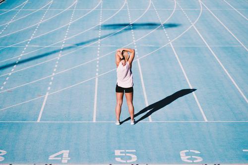 Kaukasischer junger Erwachsener, der vorher Arme auf Laufbahn ausdehnt Lifestyle Sport Leichtathletik Erfolg Stadion Mensch Frau Schuhe Fitness blau Beginn