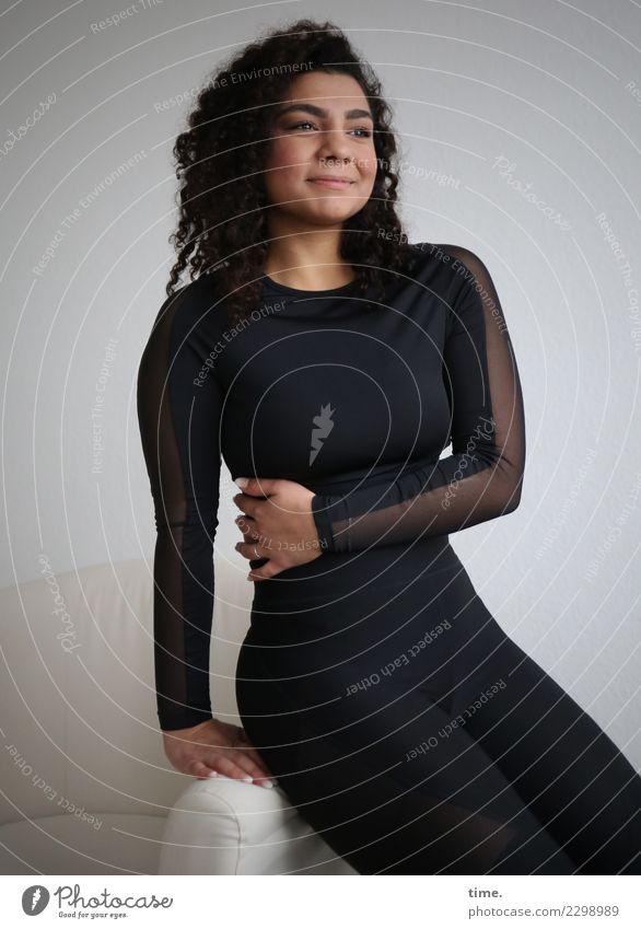 Nikolija Sessel Raum feminin Frau Erwachsene 1 Mensch T-Shirt Hose brünett langhaarig Locken beobachten festhalten Lächeln Blick sitzen Freundlichkeit
