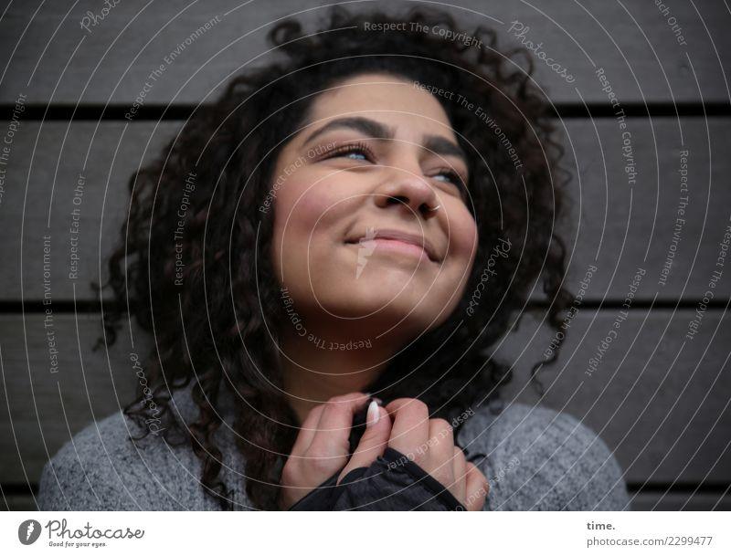 Nikolija feminin Frau Erwachsene 1 Mensch Mauer Wand Pullover brünett langhaarig Locken Erholung festhalten Lächeln Blick Freundlichkeit Fröhlichkeit schön