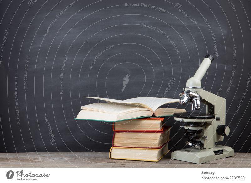 Bildungskonzeptbücher auf dem Schreibtisch im Auditorium Tisch Wissenschaften Schule lernen Klassenraum Tafel Studium Labor Buch Bibliothek Mikroskop schreiben
