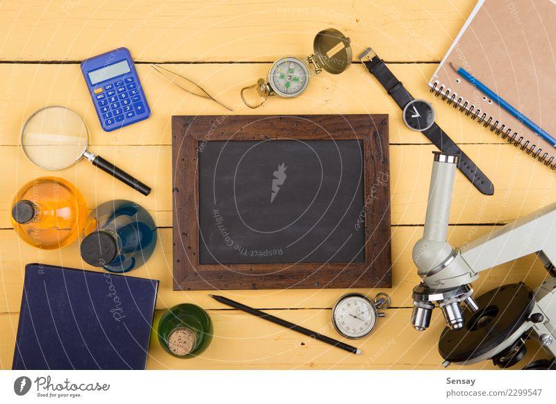 Bildungskonzept - Mikroskop auf dem hölzernen Schreibtisch gelb Holz Schule Textfreiraum Tisch lernen Buch Studium schreiben Wissenschaften Tafel Botanik Kreide