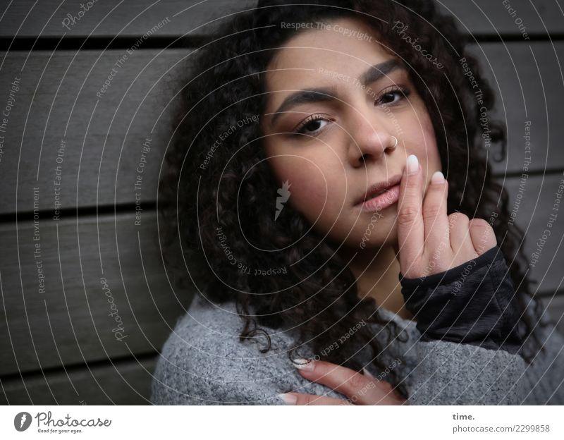Nikolija feminin Frau Erwachsene 1 Mensch Mauer Wand Pullover brünett langhaarig Locken beobachten Denken festhalten Blick dunkel schön selbstbewußt Coolness