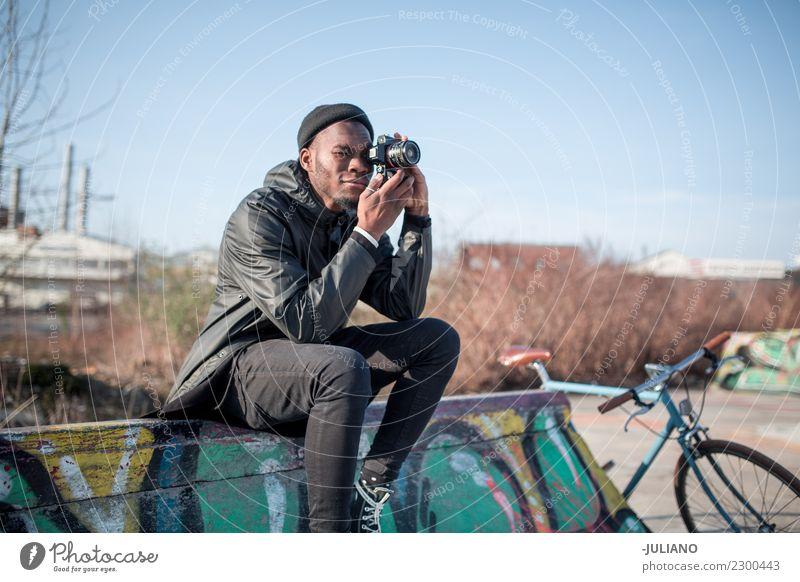 Junger moderner Mann, der auf der Halfpipe sitzt und mit der Kamera fotografiert. Stadt Stadtleben Großstadt Fotokamera Schlittschuhlaufen Skateplatz Lifestyle