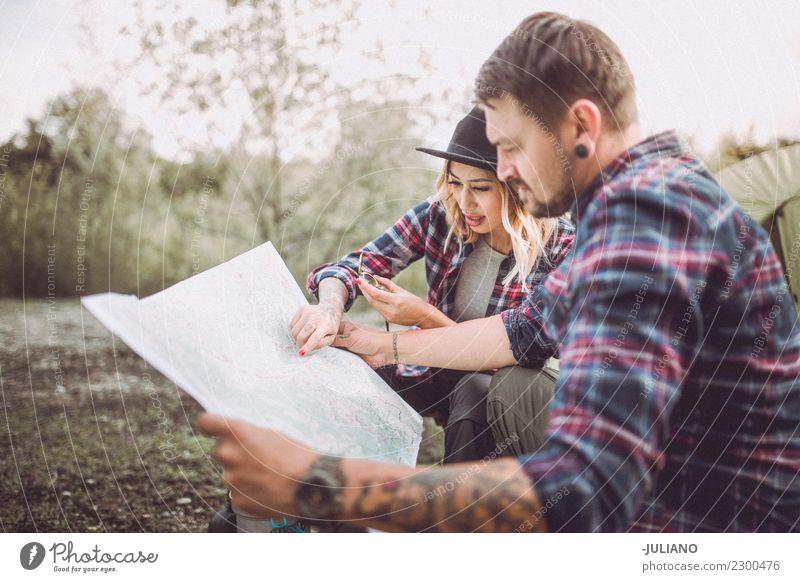 Junge kampierende Paare in der Natur, die auf Art auf Karte sucht