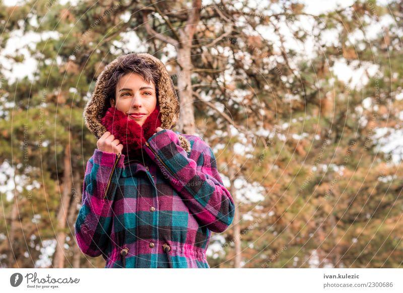 Nettes Brunettemädchen, das im Park, in tragendem Mantel und in Schal steht Lifestyle elegant Stil Glück schön Gesicht Winter Mensch Frau Erwachsene Natur