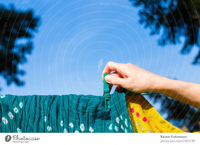 """eine Frau hängt Wäsche zum trocknen auf eine Wäscheleine Wohnung Garten Mensch feminin Hand Reinlichkeit Sauberkeit Reinheit """"waschen Hausarbeit"""