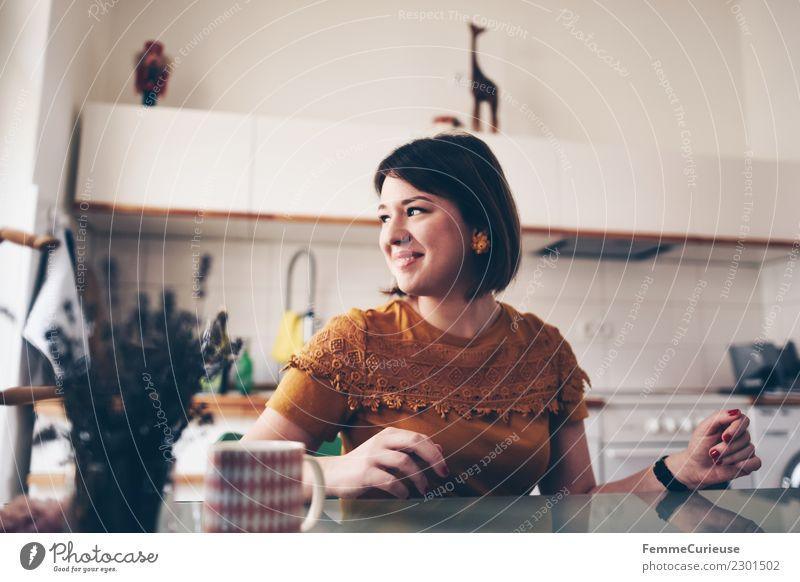 Young woman sitting at a kitchen table feminin Junge Frau Jugendliche Erwachsene 1 Mensch 18-30 Jahre Häusliches Leben Küche Küchentisch Gute Laune Vorfreude