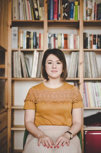 Young woman sitting on a chair (with a bookshelf behind her) Frau Mensch Jugendliche Junge Frau ruhig 18-30 Jahre Erwachsene feminin Mode Häusliches Leben