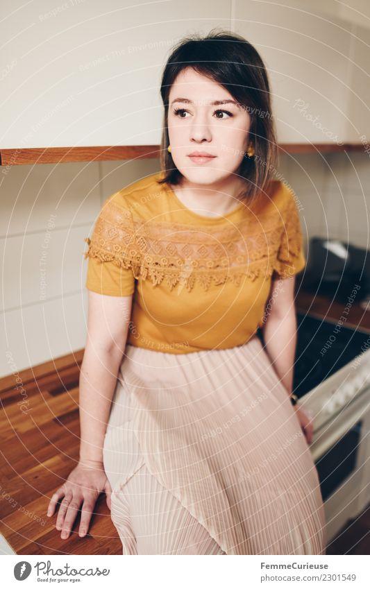 Young woman sitting in kitchen elegant Stil feminin Junge Frau Jugendliche Erwachsene 1 Mensch 18-30 Jahre Häusliches Leben Küche sitzen Holz Rock T-Shirt