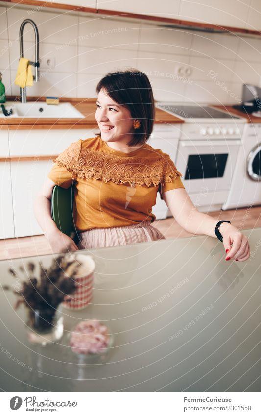 Young woman sitting in her kitchen feminin Junge Frau Jugendliche Erwachsene 1 Mensch 18-30 Jahre Häusliches Leben Zufriedenheit Küche Küchentisch Haus