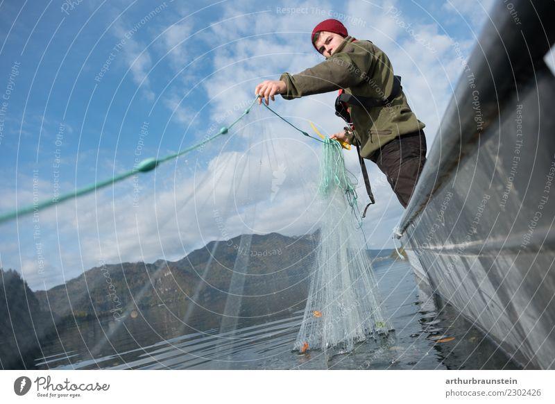 Junger Fischer im Fischerboot am See holt sein Fischernetz ein Mensch Himmel Natur Jugendliche Gesunde Ernährung Junger Mann Landschaft 18-30 Jahre Erwachsene