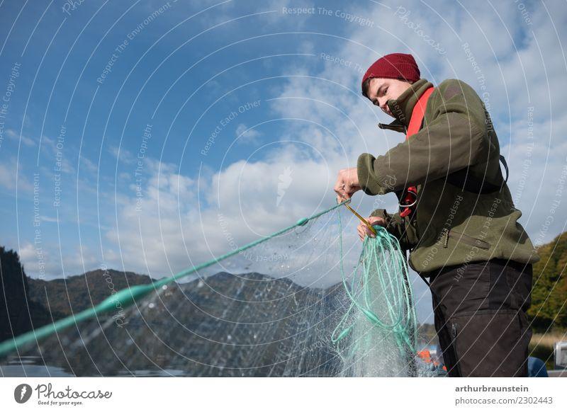 Junger Fischer holt sein Fischernetz ein jung Mann fischen See Wasser Fischfang blauer Himmel Hobby schönes Wetter sonnig Lehrberuf Azubi Beruf arbeiten