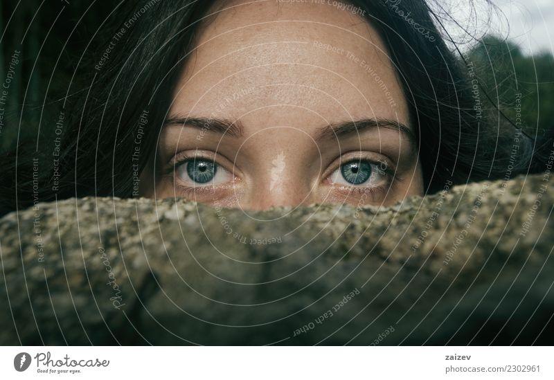 Chica de ojos azules y grandes mirando a camara por encima de una piedra tapandose la mitad de la cara Fotokamera Frau Erwachsene Stein Denken entdecken