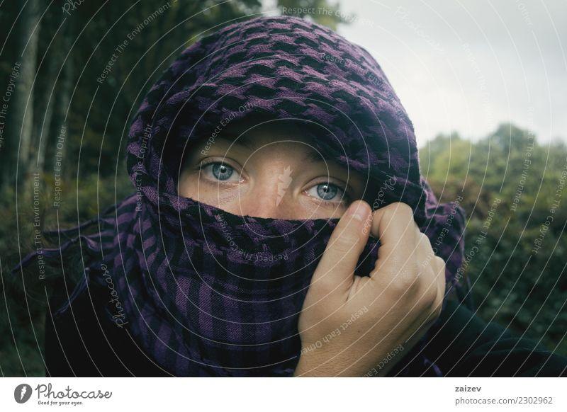 Chica de ojos azules mirando a camara tapandose la cabeza y parte de la cara con un pañuelo aguantado por su mano en la naturaleza. Lifestyle exotisch Gesicht