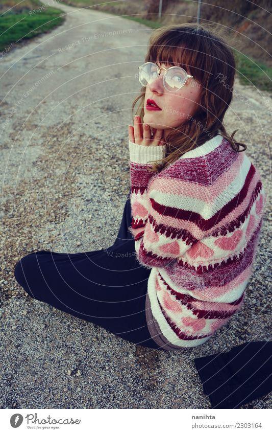 Junge Frau in Retro-Kleidung sitzt auf einer alten Straße. Lifestyle Stil Design Mensch feminin Jugendliche 1 18-30 Jahre Erwachsene Pullover Brille brünett