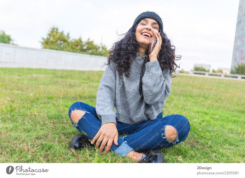 Frau, die um das Telefon sitzt auf dem Gras und dem Lächeln ersucht Jugendliche Erwachsene Lifestyle Gefühle lachen Mode Textfreiraum Stadtleben modern elegant
