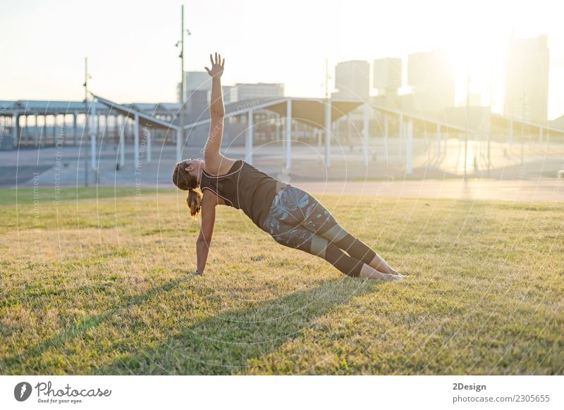 Schönes Mädchen nimmt an Yoga im Park teil Frau Natur Jugendliche grün Erholung Erwachsene Lifestyle Sport Gras Kraft sitzen harmonisch Beautyfotografie
