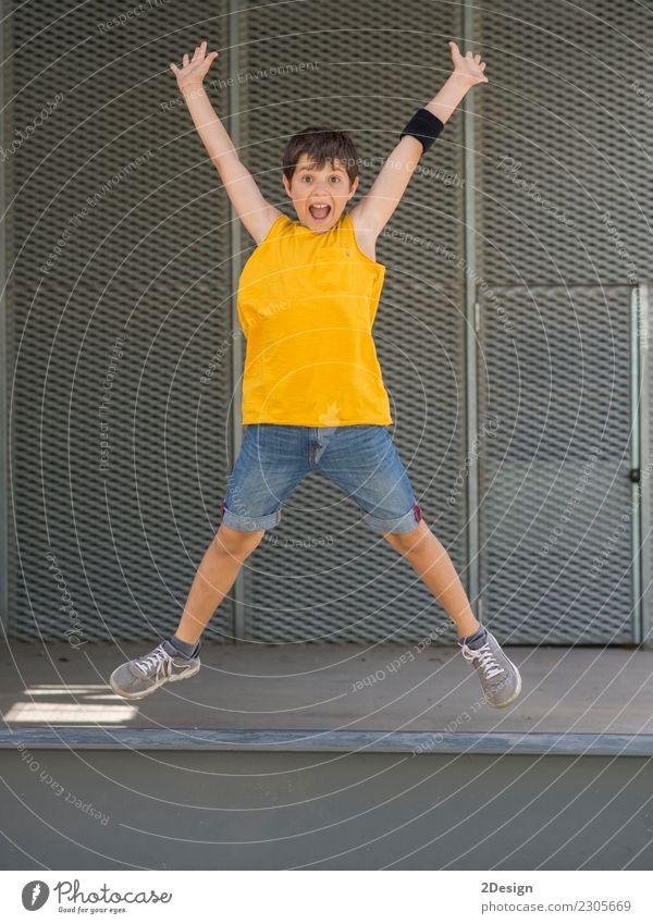 Ein junges jugendlich tragendes gelbes T-Shirt und Springen Lifestyle Freude Freiheit Sommer Sport Erfolg Kind Junge Mann Erwachsene Jugendliche Arme Wiese