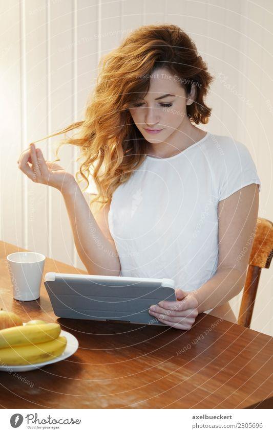 junge Frau mit Tablet Computer am Frühstückstisch Frucht Kaffee Lifestyle Erholung Freizeit & Hobby Häusliches Leben Wohnung Tisch Küche Entertainment Notebook