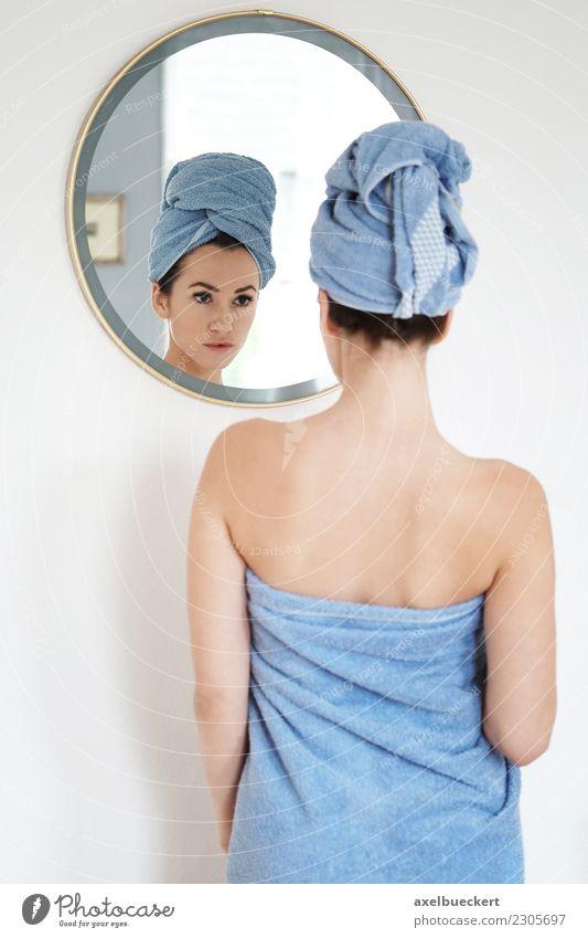 junge Frau in Handtuch gehüllt betrachtet sich im Spiegel Lifestyle schön Körperpflege Wellness Wohnung Schlafzimmer Bad Mensch feminin Junge Frau Jugendliche