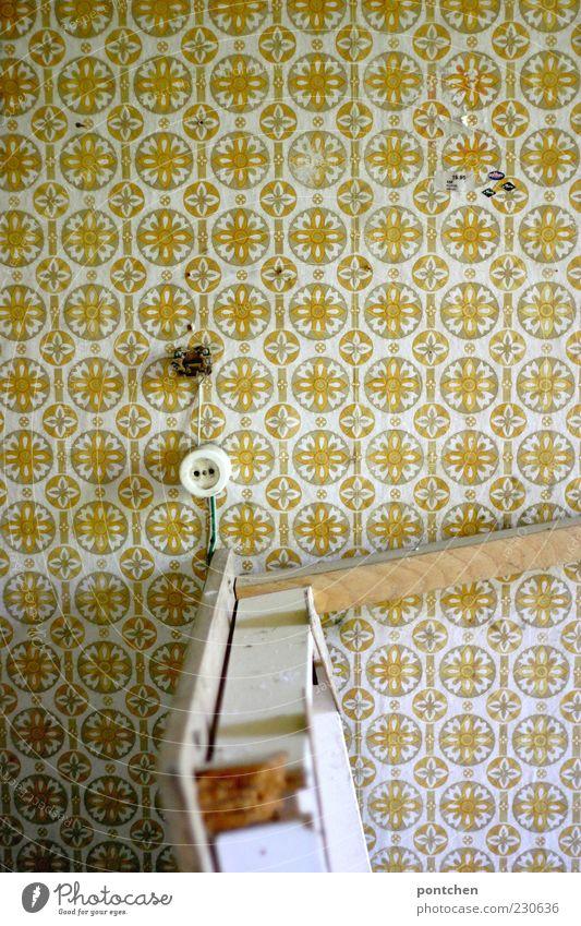 70er Kaputter Tisch steht hochkant in einem Zimmer das mit einer gemusterten Tapete tapeziert ist. Vintage, vergangen, lost place. Verfall Wohnung Renovieren