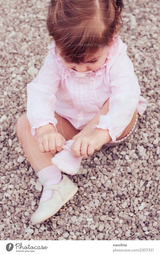 Kleines Mädchen, das auf ihre Socken sich setzt Lifestyle Stil Kindererziehung Bildung Mensch feminin Kleinkind Kindheit 1 1-3 Jahre Mode Bekleidung Hemd