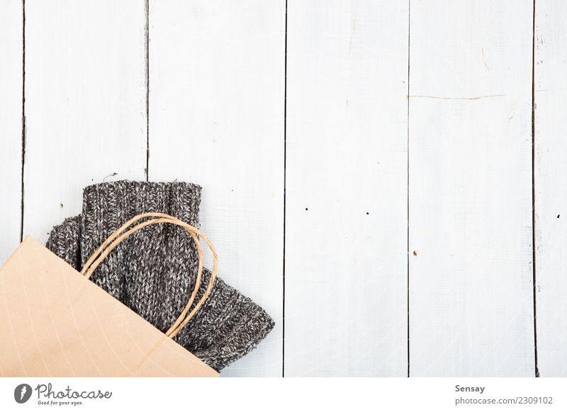 gestrickter Winterpullover auf Holzuntergrund Lifestyle kaufen Stil stricken Schreibtisch Tisch Industrie Herbst Wärme Mode Bekleidung Pullover Stoff weich grau