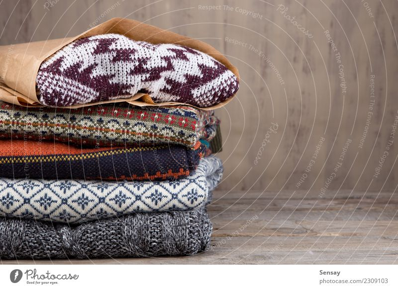 Stapel von gestrickten Winterstrickjacken auf hölzernem Hintergrund Lifestyle kaufen Stil stricken Schreibtisch Tisch Industrie Herbst Wärme Mode Bekleidung