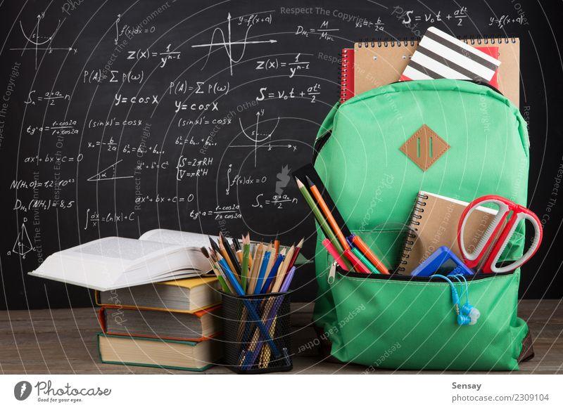Bildungskonzept - Schulrucksack mit Büchern und anderem mehr Schreibtisch Tisch Kind Schule lernen Klassenraum Tafel Werkzeug Schere Menschengruppe Buch