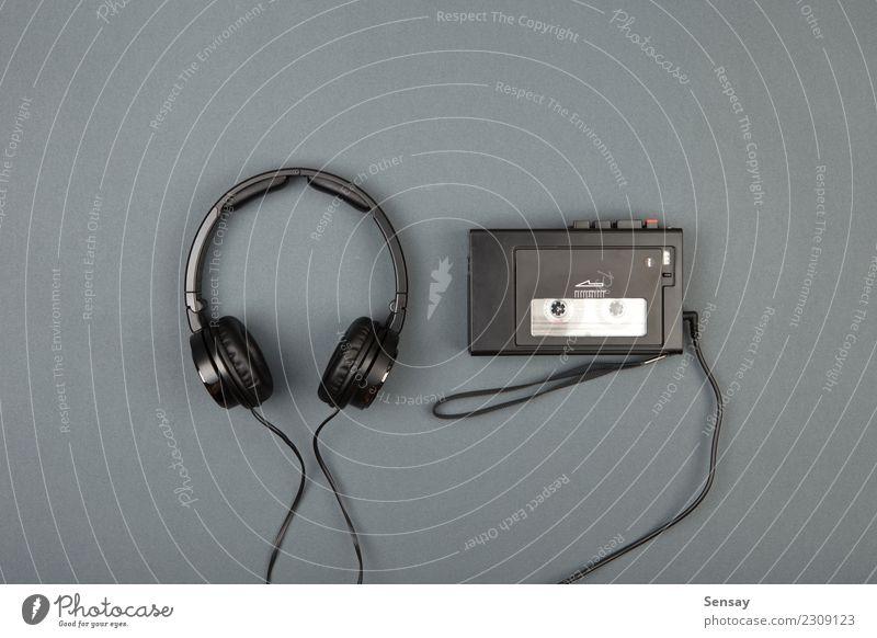 Retro-Kassettenspieler mit Kopfhörer auf grauem Hintergrund Stil Freizeit & Hobby Spielen Schreibtisch Musik Telefon Headset Technik & Technologie Felsen alt