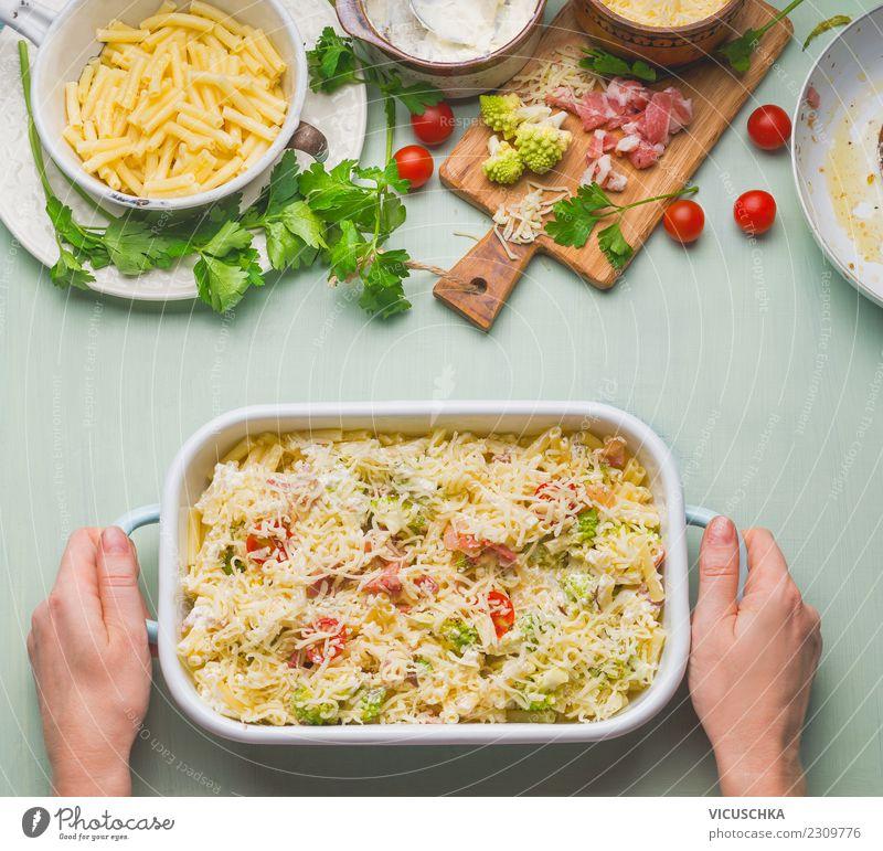 Weibliche Hände halten Auflaufform mit Nudelauflauf Frau Hand Essen Erwachsene gelb feminin Lebensmittel Stil Design Tisch Küche Essen zubereiten Geschirr