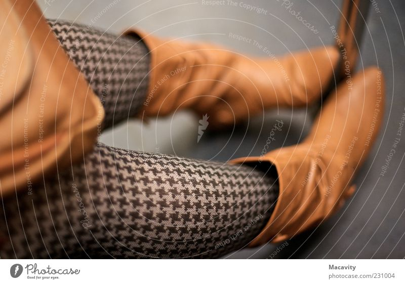 In der Metro II schön feminin grau Stil Beine braun Schuhe sitzen warten Lifestyle Bekleidung retro einfach Stiefel frieren Strümpfe