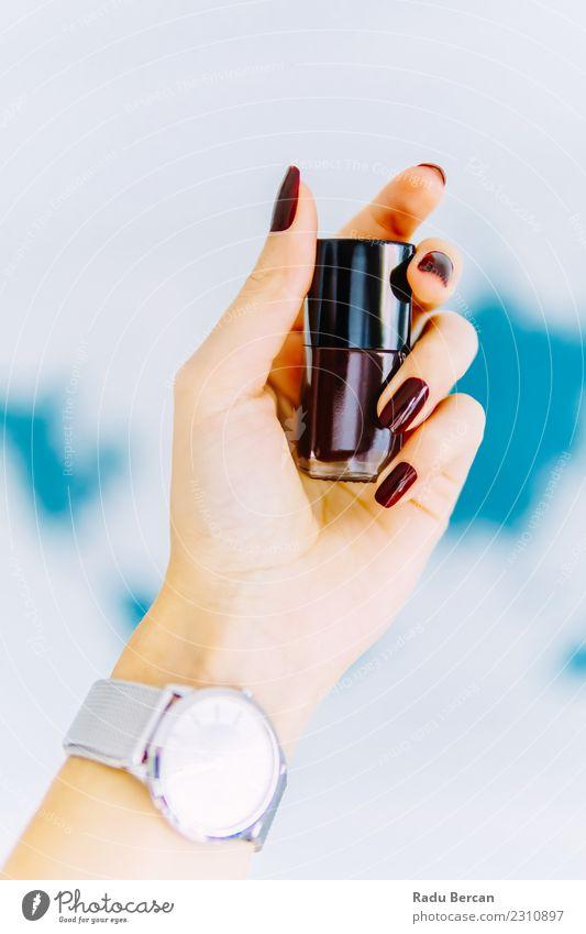 Frauen-Hand, die eine Flasche roten Nagellack hält Lifestyle elegant Stil Design schön Maniküre Schminke Wellness Uhr Mensch feminin Junge Frau Jugendliche