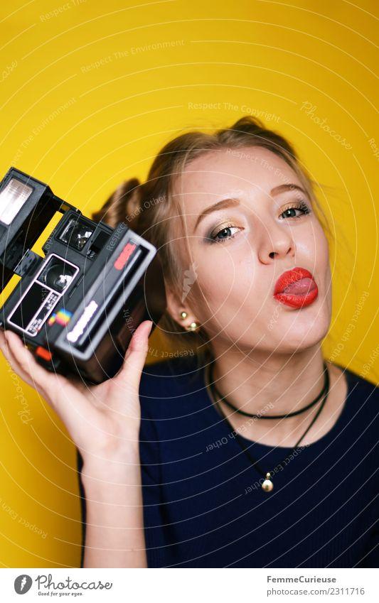 Young woman holding an instant camera Frau Mensch Jugendliche Junge Frau rot 18-30 Jahre Erwachsene gelb Lifestyle feminin Stil Freizeit & Hobby Kreativität
