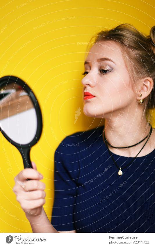 Young woman looking at herself in a mirror Lifestyle Stil feminin Junge Frau Jugendliche Erwachsene 1 Mensch 18-30 Jahre schön gelb Dutt Spiegel Spiegelbild