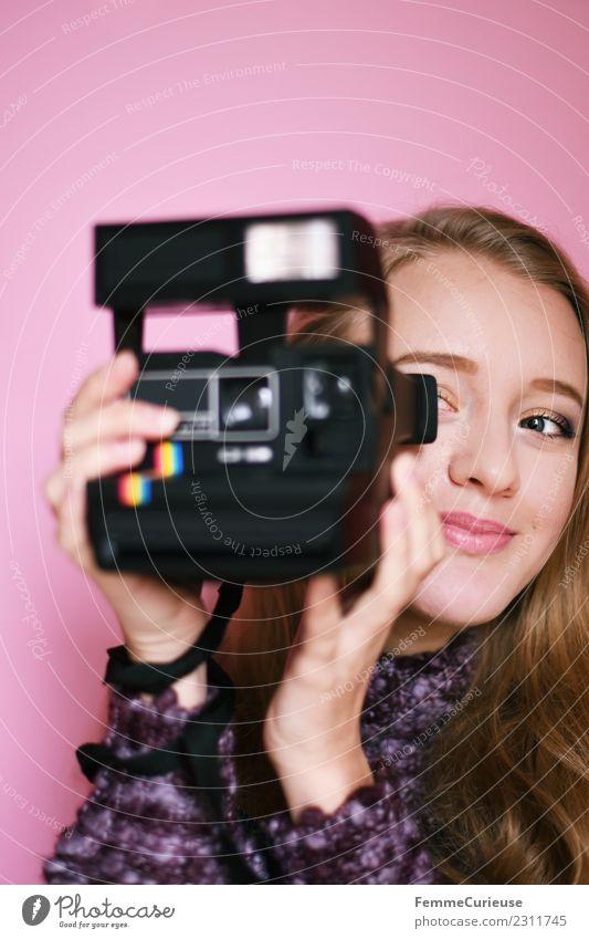 Young woman taking pictures with an instant camera Frau Mensch Jugendliche Junge Frau 18-30 Jahre Erwachsene feminin rosa Kreativität Fotografie analog Pullover