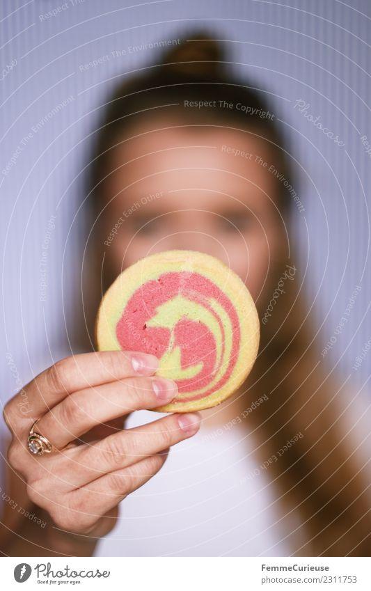 Young woman showing cookie into the camera Lebensmittel Junge Frau Jugendliche Erwachsene 1 Mensch 18-30 Jahre genießen Mürbeplätzchen Cookie Backwaren Süßwaren