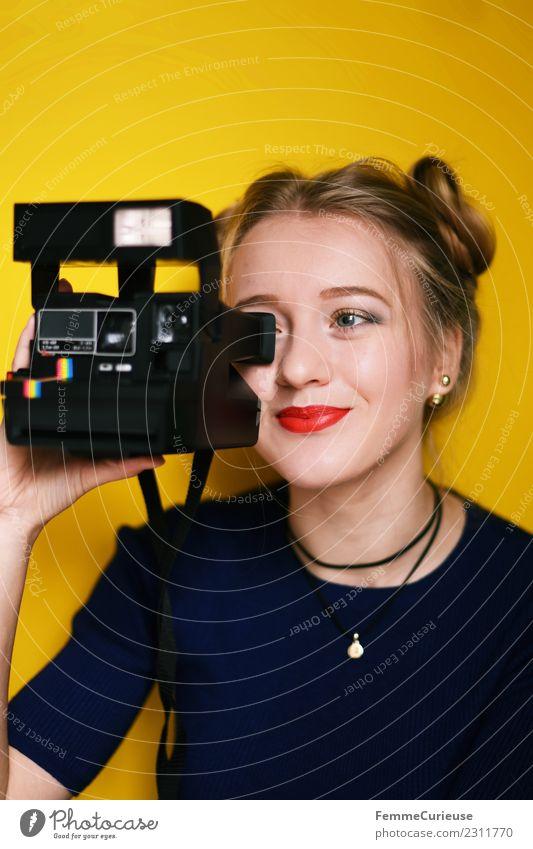 Young woman taking pictures with an instant camera Frau Mensch Jugendliche Junge Frau rot 18-30 Jahre Erwachsene gelb feminin Mode Freizeit & Hobby Fröhlichkeit